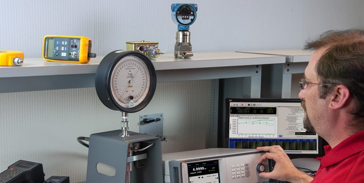 Technician Calibrating a Dial Gauge in House with a Pressure Calibrator